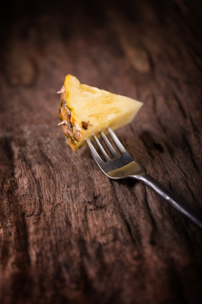 Pineapple slices and pineapple shelled asian-style on the old wooden background Premium Photo