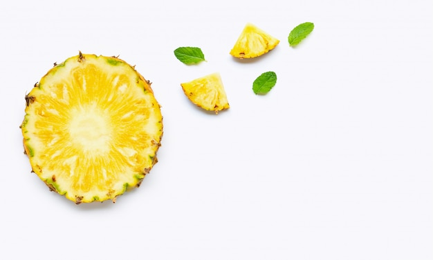 Pineapple slices with mint leaves on white background. Premium Photo