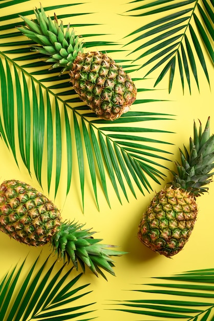 Pineapple and tropical palm leaves on yellow background. creative flat lay with copy space. Premium Photo