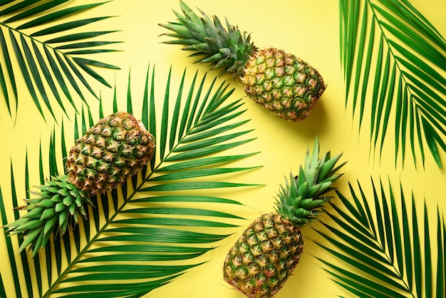 Pineapple and tropical palm leaves on yellow background. summer concept. Premium Photo