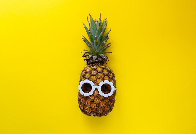 Pineapple in white sunglasses on the colorful background, creative summer concept Premium Photo