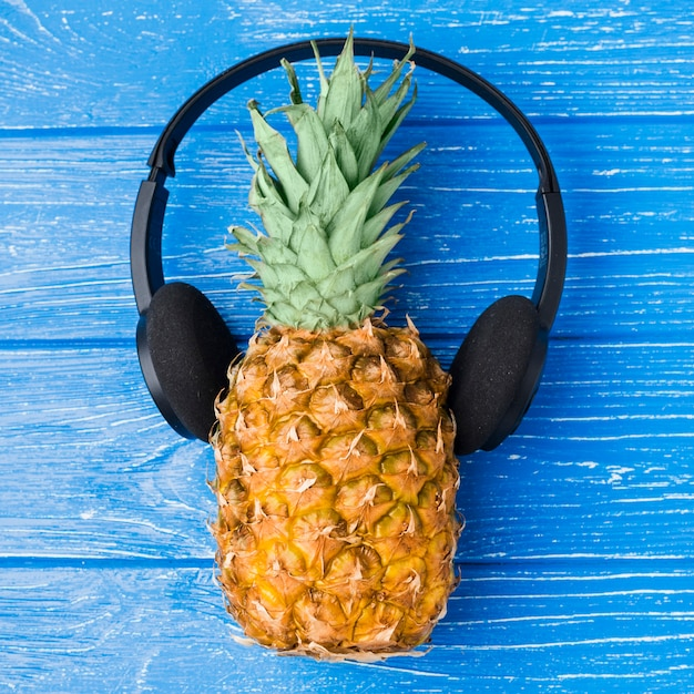 Pineapple with headphones on board Free Photo
