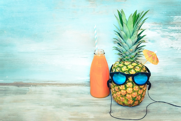 Pineapple with sunglasses and headphones and a bottle of juice in front of a blue wood Premium Photo