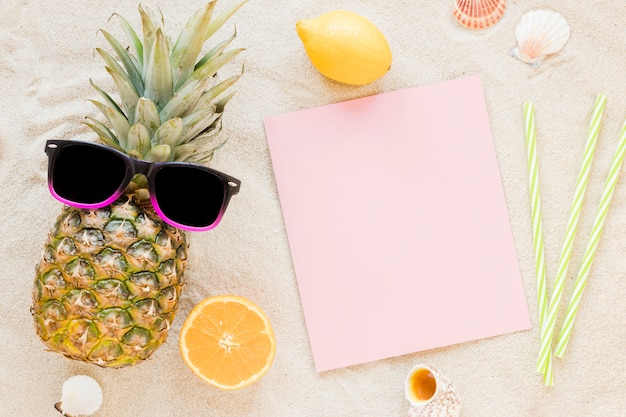Pineapple with sunglasses and paper on sand Free Photo