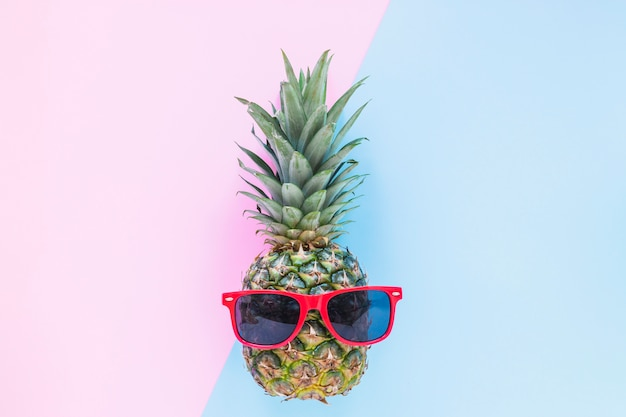 Pineapple with sunglasses on table Free Photo