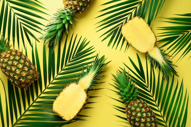 Pineapples and tropical palm leaves on pastel yellow background. summer concept. Premium Photo