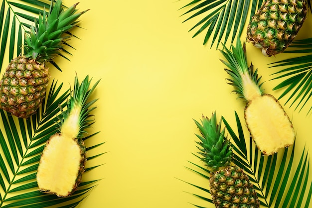 Pineapples and tropical palm leaves on punchy pastel yellow background. summer concept Premium Photo