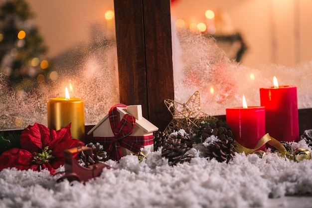 Pinecones on fake snow and canddles Free Photo