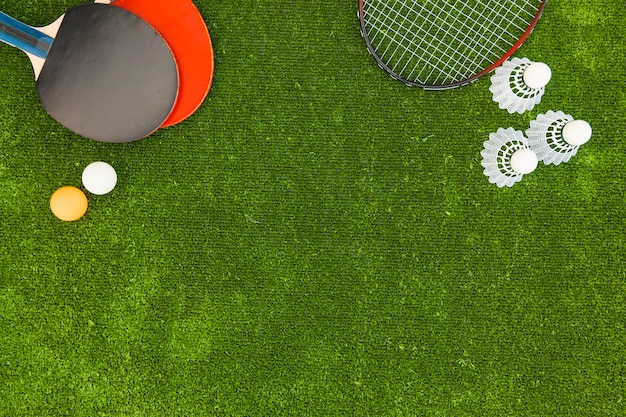 Ping-pong balls; shuttlecock; badminton and rackets on green turf Free Photo
