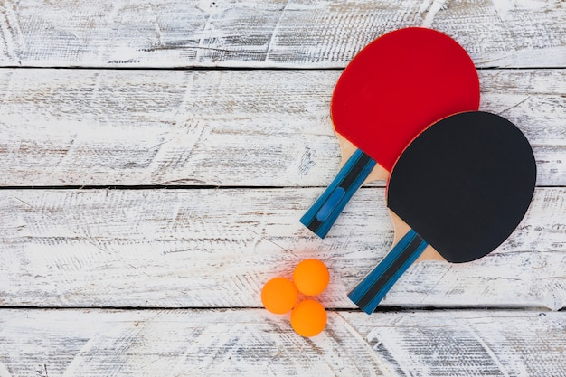 Ping pong balls and wooden racket on white wooden background Free Photo