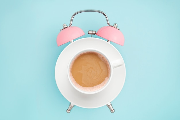 Pink alarm clock and coffee cup on blue . breakfast time . minimal style Premium Photo