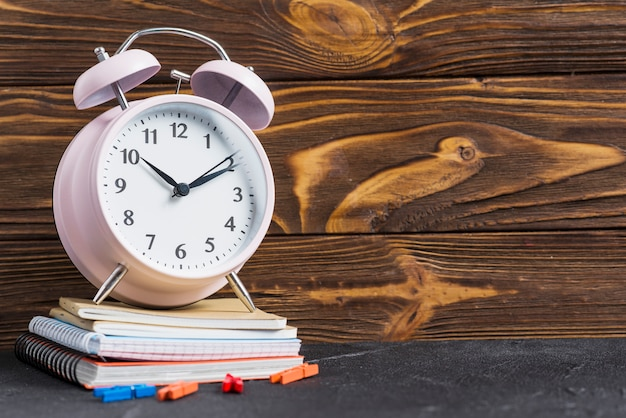 Pink alarm clock over the stacked of notebooks and clothes peg against wooden wallpaper Free Photo