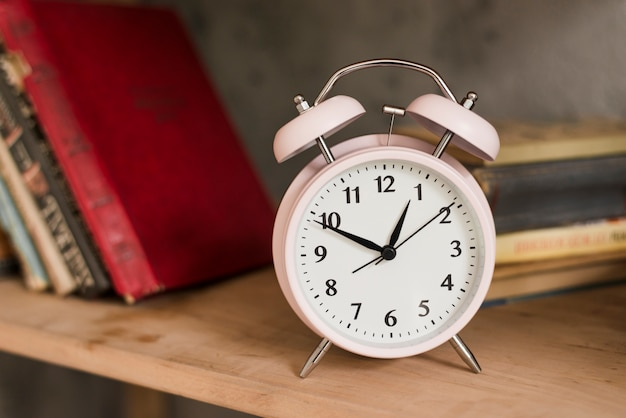 Pink alarm clock on wooden bookshelf Free Photo