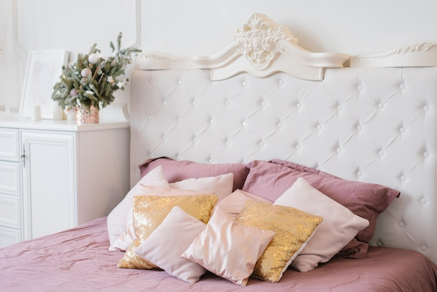 Розовые и золотые подушки на большой двуспальной кровати в спальне украшены на рождество Premium Фотографии