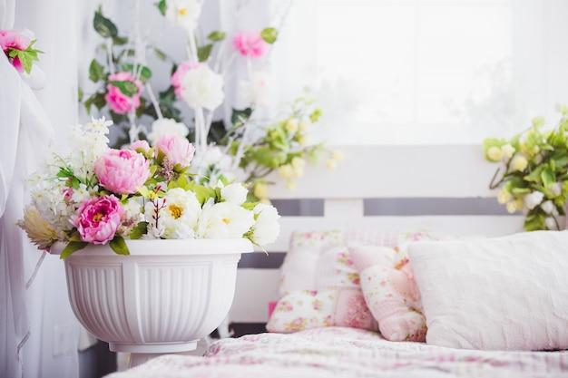 Розовые и белые цветы в вазе возле кровати Premium Фотографии