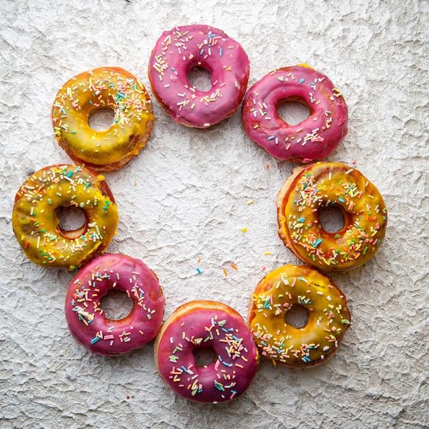 織り目加工の白地に円形のピンクと黄色のドーナツ。上面図。 無料写真