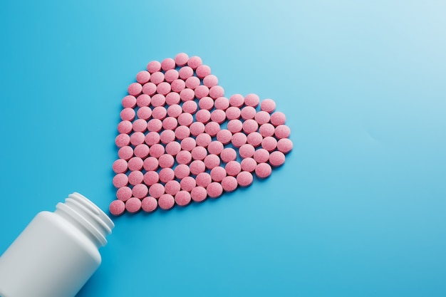 Pink b12 pills in the shape of a heart on a blue background Premium Photo