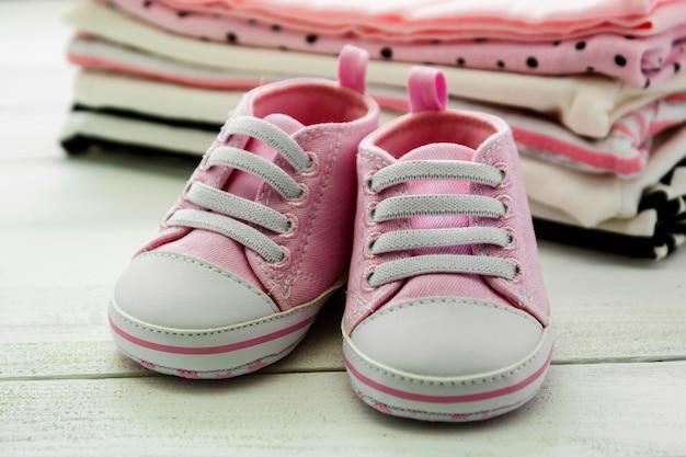 Розовая детская обувь и новорожденная одежда. концепция материнства, образования или беременности с космосом экземпляра. Premium Фотографии
