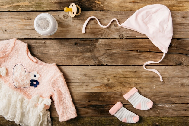 Pink baby's dress with headwear; pair of socks; milk bottle and pacifier on wooden table Free Photo