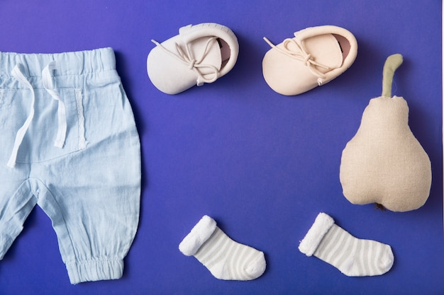 Pink baby shoes; sock and baby's pant with stuffed pear on bright blue background Free Photo