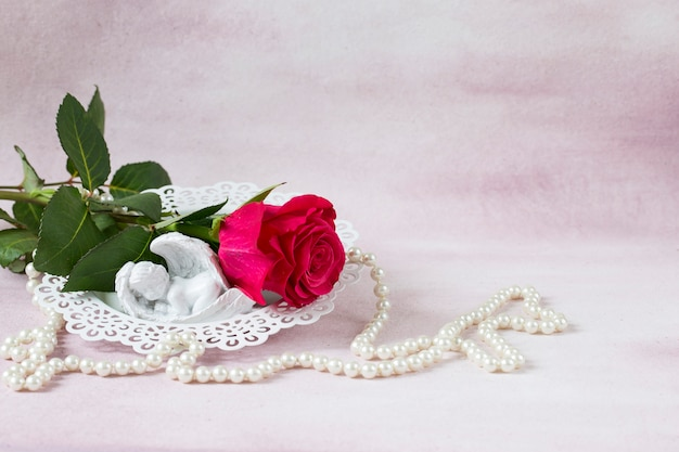 On a pink background is a bright pink rose, pearl beads and angel figure Premium Photo