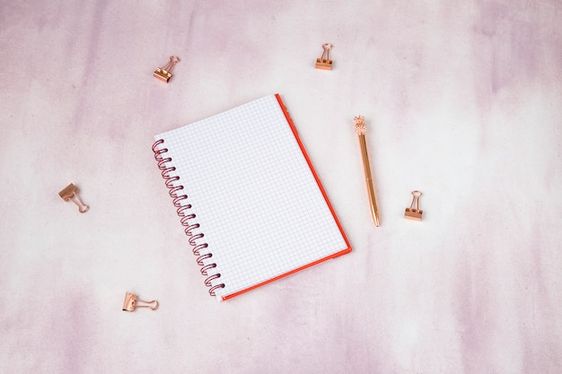 On a pink background notepad, paper clips, pen in rose gold Premium Photo