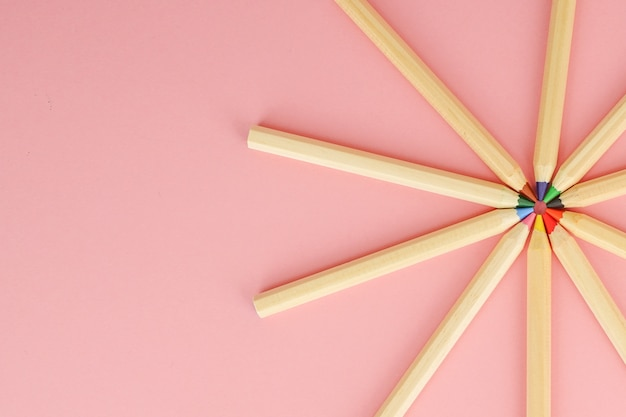 Pink background with wooden colorful ordinary pencils. back to school. Premium Photo