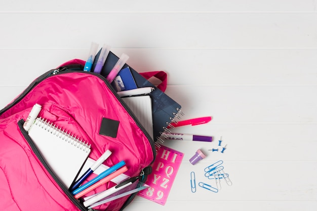 Pink backpack with school supplies top view Free Photo