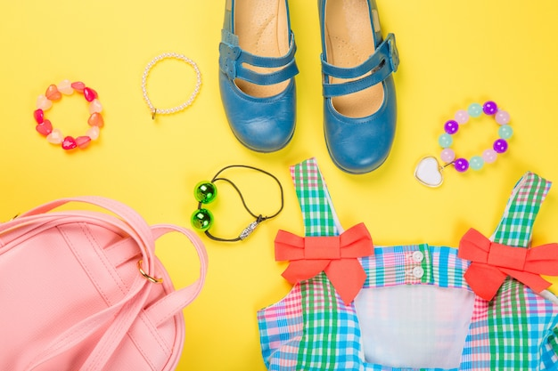 Pink bag with colorful dress, circlet, hair ties and shoes Premium Photo