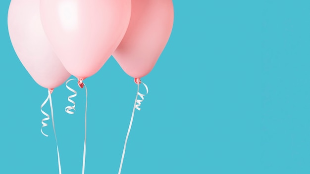 Pink balloons with ribbons on blue background Free Photo