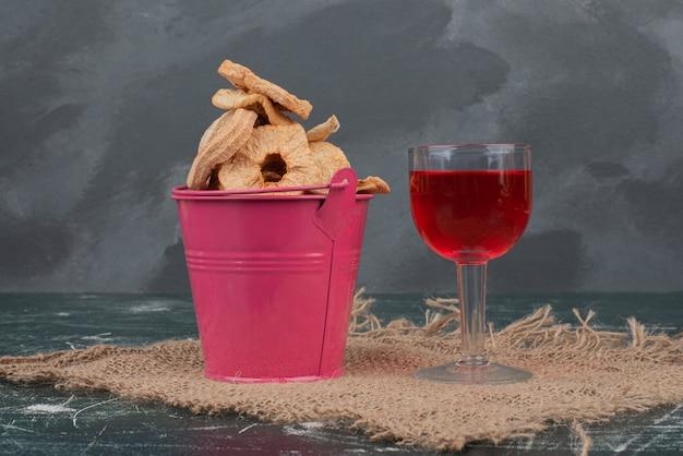 大理石の壁にドライフルーツとジュースのガラスが入ったピンクのバスケット。 無料写真