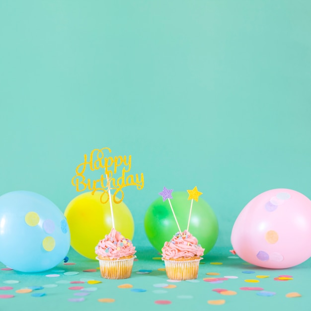 Pink birthday cupcakes with balloons Free Photo