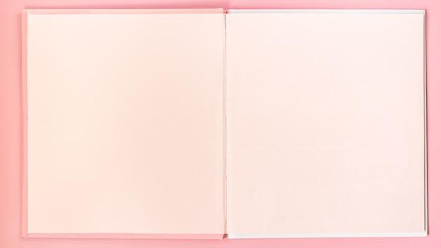 ピンクの空白のページはピンクのテーブルに本をスケッチします Premium写真