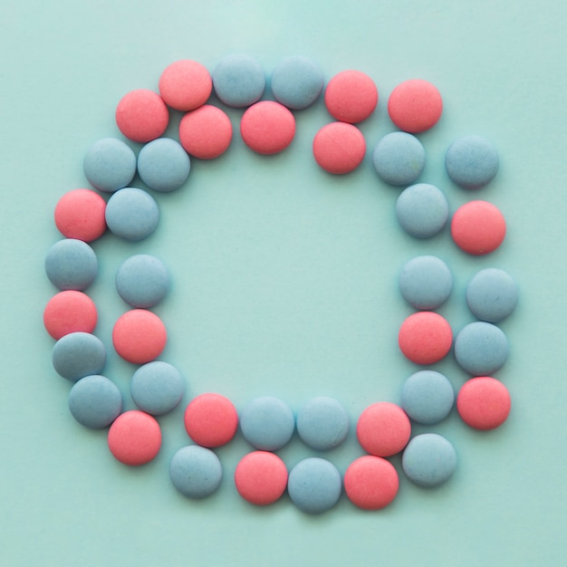 Pink and blue candies arranged in circular shape over the colored backdrop Free Photo