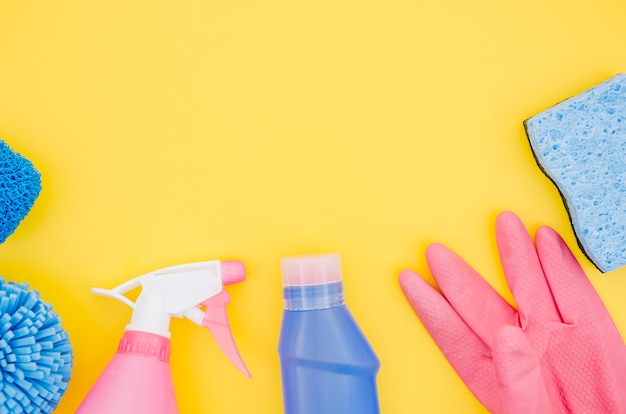 Pink and blue cleaning supplies on yellow backdrop Free Photo