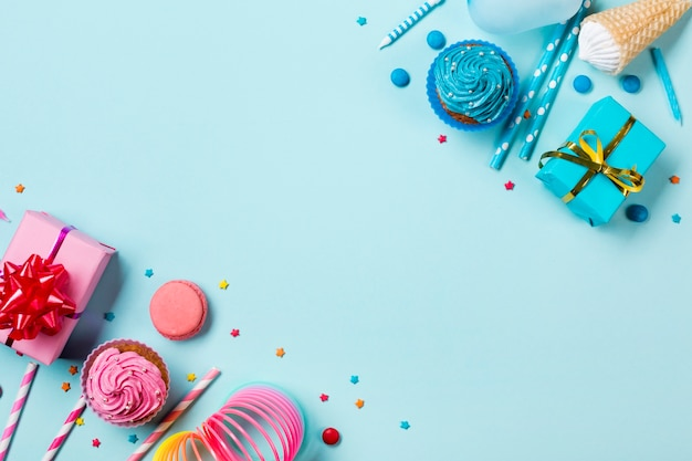 Pink and blue colored party items with confectionery on colored backdrop Free Photo