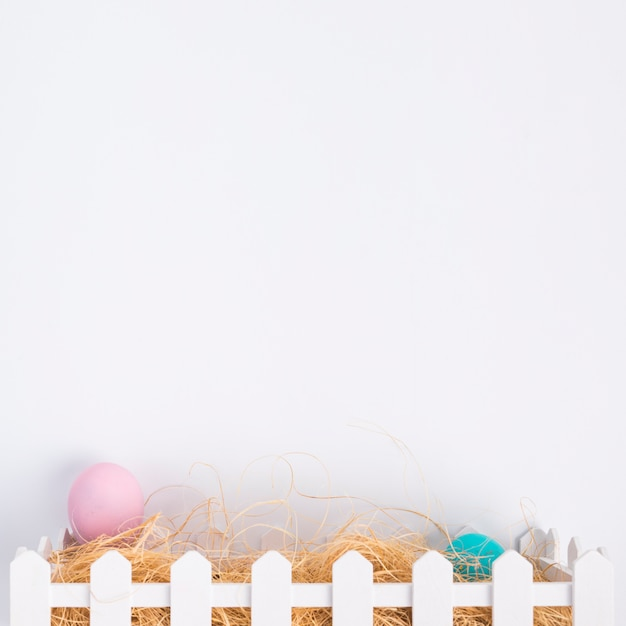 Pink and blue easter eggs between hay in box Free Photo