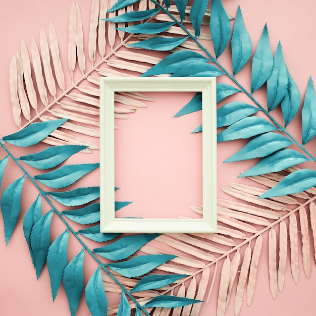 Pink and blue leaves on pink background with blank frame Free Photo
