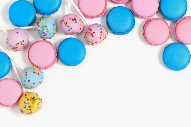 Pink and blue macaroons and cake pops on white Premium Photo