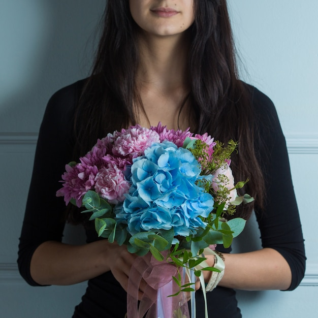 Pink and blue tonned flower bouquet in the hands of a woman Free Photo