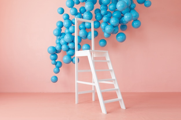 Pink bright studio interior with white ladder and hanging blue balls. Free Photo