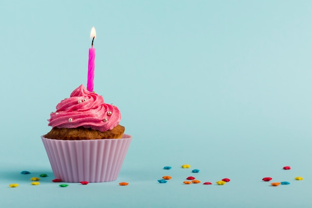 Pink burning candles on decorative muffins with colorful star sprinkles against blue backdrop Free Photo