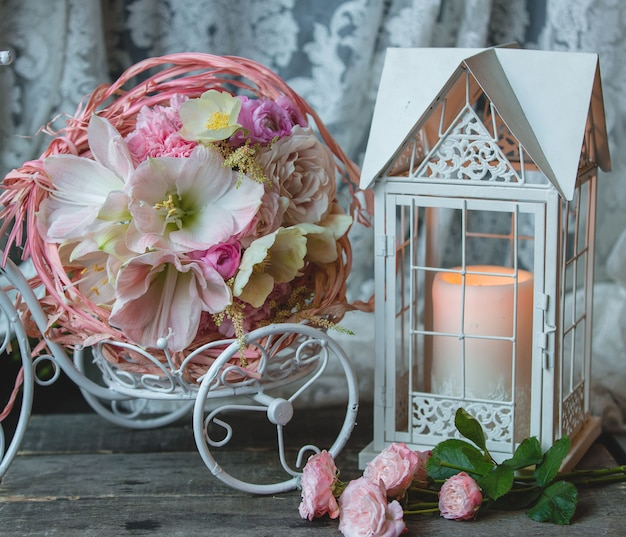 Pink candle in a fake cage, small wreath of flowers. Free Photo