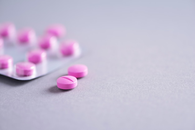 Розовая капсула, таблетки, витамины на сером фоне. копировать пространство куча лекарств, лечение простуды. лечение женской болезни. баннер Premium Фотографии