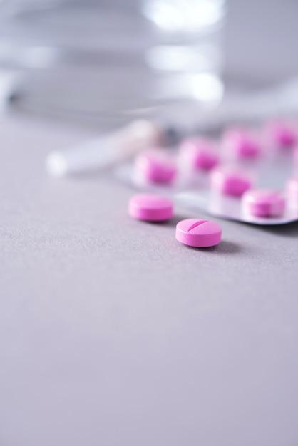 Розовая капсула, таблетки, витамины на сером фоне. копировать пространство куча лекарств, лечение простуды. лечение женской болезни. Premium Фотографии