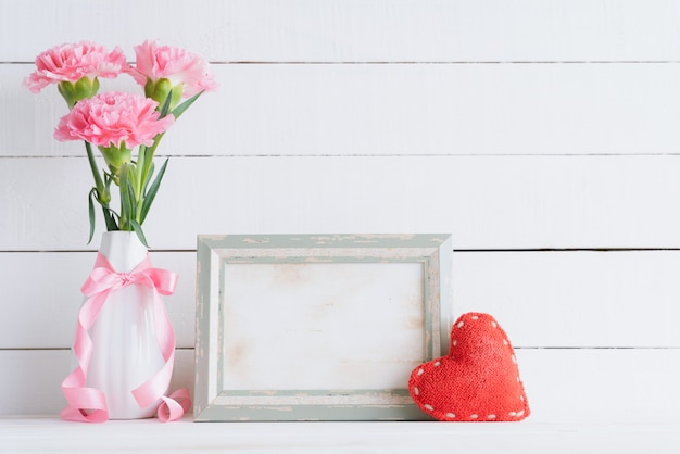 Pink carnation flower in vase with old vintage picture frame and red heart Premium Photo