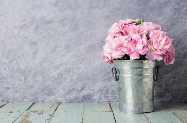 fdbbc7cd8 Pink carnation flowers in zinc bucket on old wood Photo   Premium ...