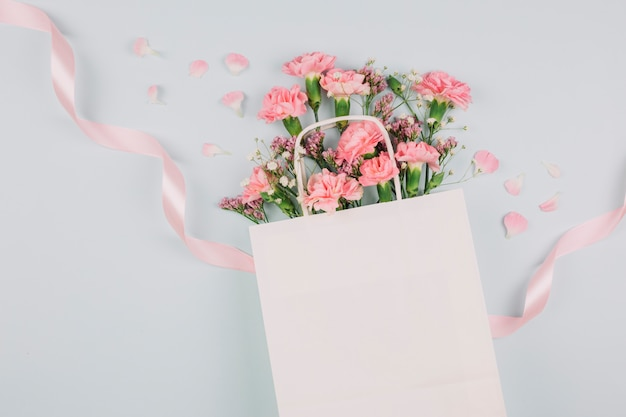 Pink carnations; limonium and gypsophila flowers inside the white shopping bag with pink ribbon on white backdrop Free Photo