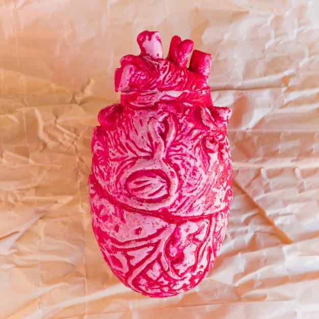 Cuore umano in ceramica rosa su carta Foto Gratuite