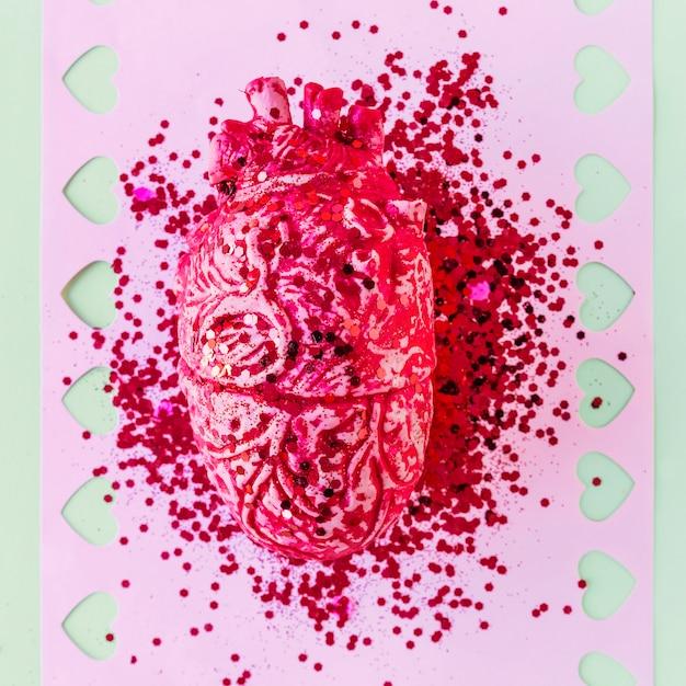 Cuore umano in ceramica rosa con lustrini su carta Foto Gratuite